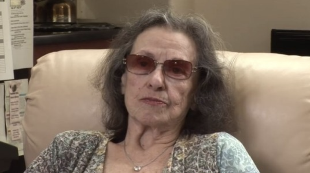 Katherine MacGregor older wearing sunglasses whilst sitting on a sofa