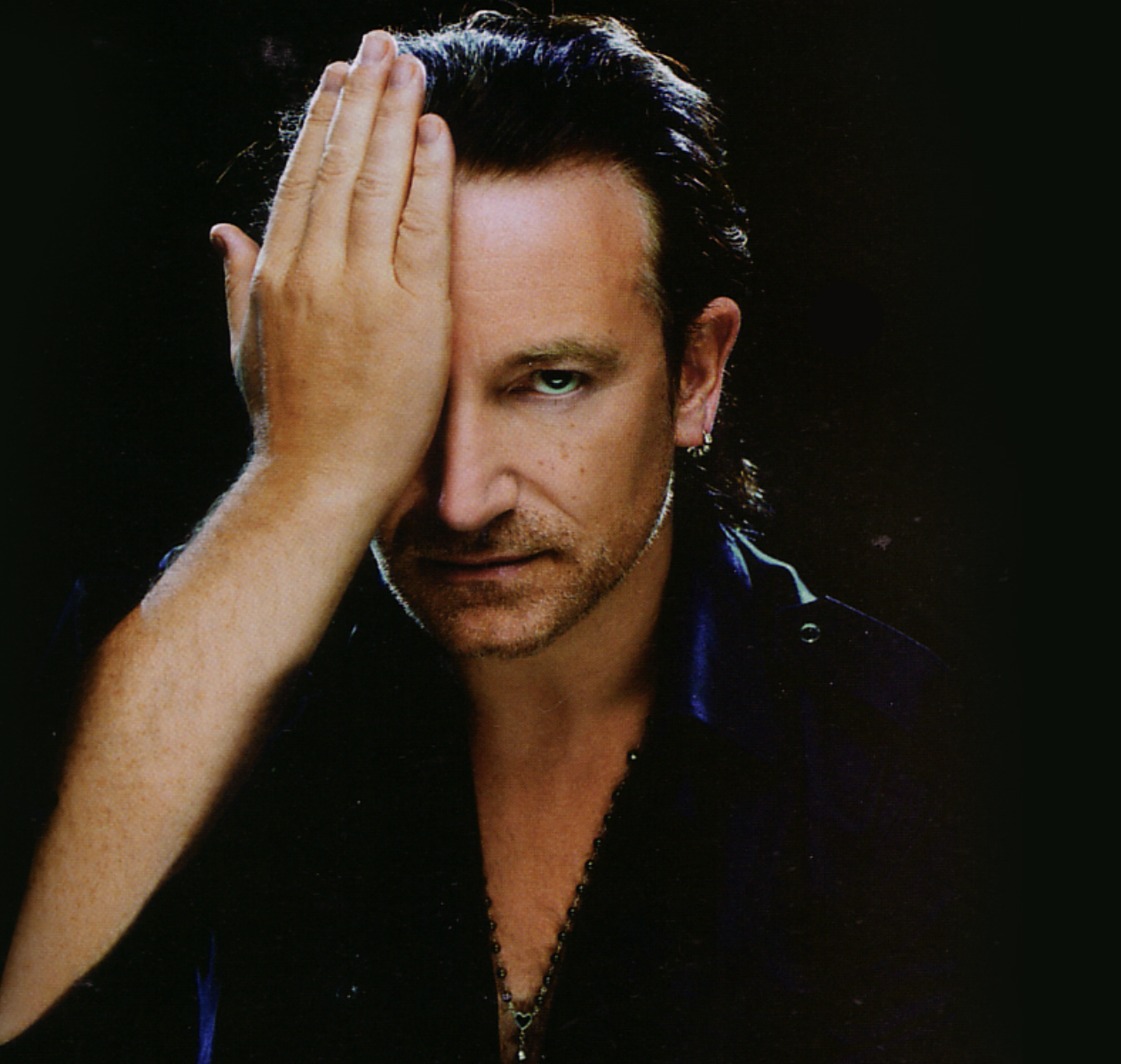 bono covering half of his face with his hand